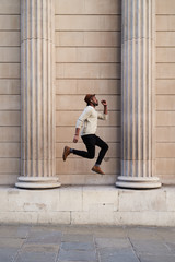 Stylish man in earphones jumping over stone columns.