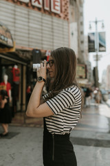 Woman Photographer Shooting a Camera in a City