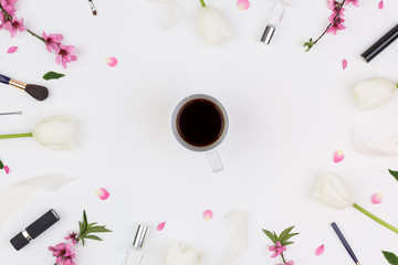 cheerfulness, lifestyle, cosmetics concept. top view of cup of espresso that placed in the center of the frame crafted of flowers and blooming brunches and supplies for make up