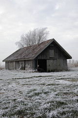Rustic old barn in frozen field in winter