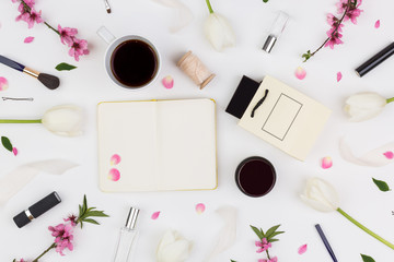 make up, planning, motivation concept. top view of natural delicate tulips and brunches of blooming cherry that surround wonderful woman decorative cosmetics few cups of coffee