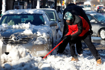 Men shovel snow from a car following winter snow Storm Grayson in the Queens borough of New York