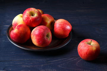 Apples in a plate on a dark wooden background