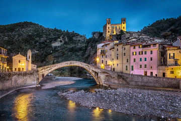 Fototapete - Dolceacqua town at dusk, Liguria, Italy, 15th century Romanesque bridge (Ponte Vecchio), over the Nervia creek, colorful houses and ruins of the 13th century castle