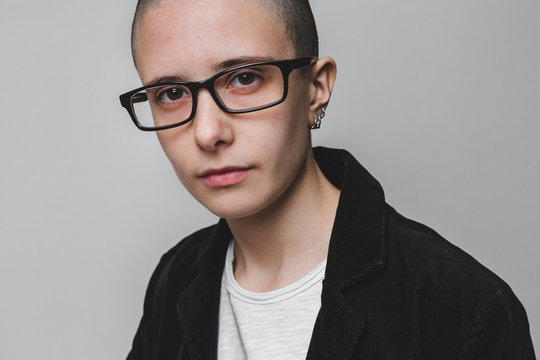 Person with shaved head and eyeglasses