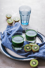 Two glasses of kiwi and kale smoothie drink on a table.