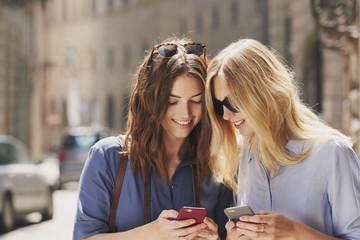 Beautiful woman friends smiling happy using smart phone technolo