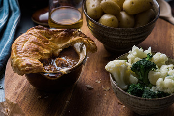 Homemade steak pie topped with pastry and served with vegetables.