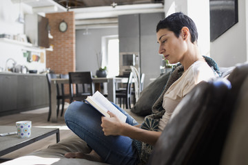 Woman reading a book on the couch in living room
