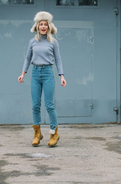 beautiful cheerful girl in a bright boots jumping on the background of blue wall