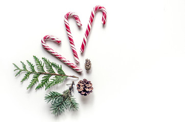 New Year's unusual composition with spruce branches, sweets and cones. Christmas background for presentation of work or text. Beautiful greeting card. View from above. Copy space