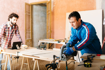 Carpenter working with circular saw in workshop.