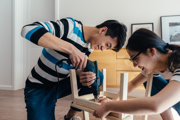 Young couple assembling flat-pack furniture