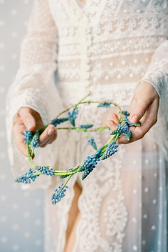 Female holding wreath of small blue flowers