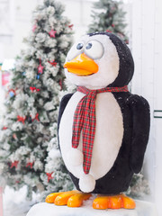 A toy penguin standing against Christmas trees surrounded with gift boxes. Christmas and New Year concept.