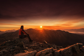 Man seating on the top of mountain at sunrise, hiking and climbing
