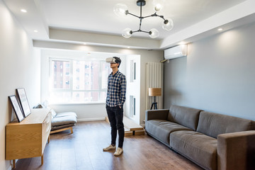 Young man wearing virtual reality headset at home