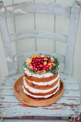 Delicious naked cake with cream and colored fruits