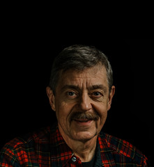 Portrait of a man in plaid button-up shirt isolated on a black background