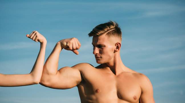 Bodybuilder with strong hand biceps, triceps contest with female hand