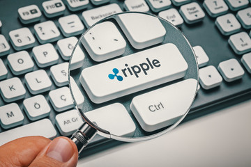 magnifying glass in hand focused on computer key with ripple coin logo. cryptocurrency concept