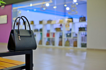 black bag in the shop window in the mall. Luxury and fashionable brand window display. New collection of casual clothings and bags.