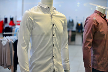 Fashion clothes on mannequins in a shopping center. Sweaters and shirts.