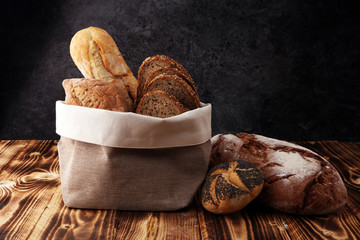 Different kinds of bread and bread rolls on wooden background. Kitchen or bakery poster design.