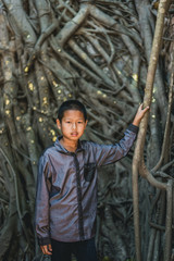 Portrait of Asian boy with the root wall