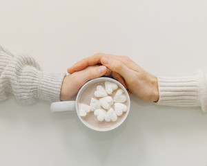 People holding hands and cocoa cup