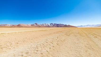 Dirt road at high altitude with sandy desert and barren volcano range on the Andean highlands. Road trip to the famous Uyuni Salt Flat, travel destination in Bolivia.