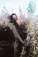 Portrait of female hiding behind the bouquet