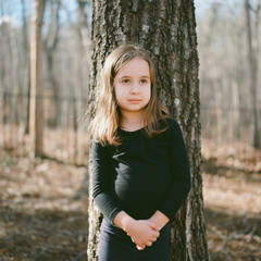 Beautiful young girl leaning up against a tree