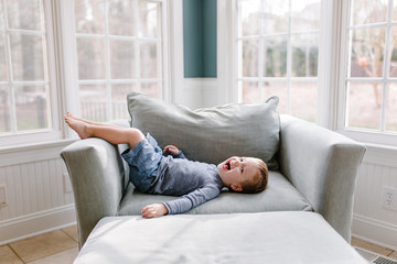 Cute young boy lying on an oversized chair laughing