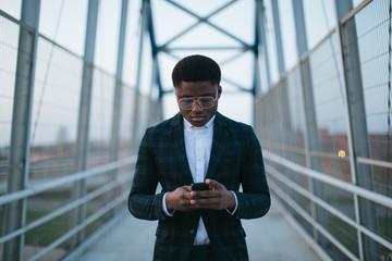 man using phone on the bridge