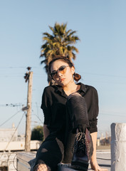 portrait of young female woman on rooftop in sunny California wearing sunglasses