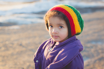 Portrait of a pretty young child wearing a vibrant colored hat, looking intently at the camera