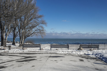 3 park benches sitting empty on snow covered beach