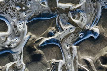Detail of water and patterns on beach, close up