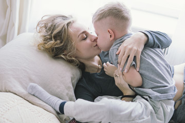 beautiful young mother kissing her son