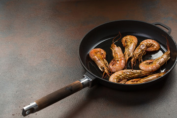 Giant prawns on hot pan stir fried in butter. Large tiger shrimps or langostinos in a frying pan