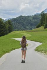 Traveler girl walking alone countryside road on wanderlust adven