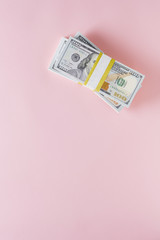Overhead view of stack of 100 dollar bills on pink background