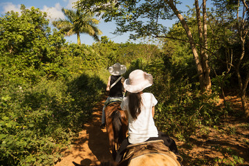 Foto auf Leinwand Karibik Horseback riding in the tropical forest of Vinales (Cuba)