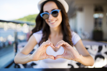 With love for everyone. Beautiful young cheerful girl showing heart by hands to camera