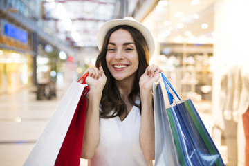 Attractive trendy woman in hat with shopping bags stands at shop in big mall
