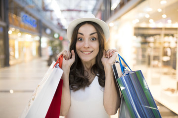 Smiling woman with shopping bags in the big mall