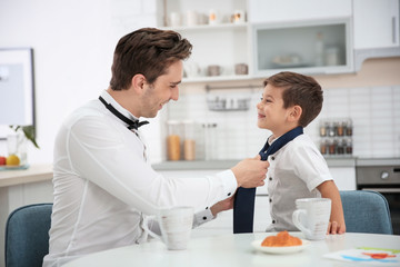 Young father helping his little son to knot necktie at home