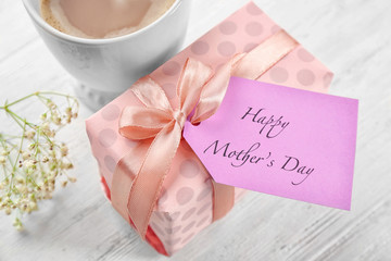 Happy Mother's day greeting with cup of aromatic coffee and gift box on table