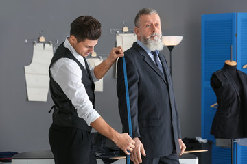 Tailor taking client's measurements in atelier